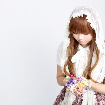 「花のアクセサリーを両手いっぱいに持つゆるふわな女の子」の写真素材