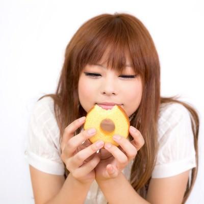 「バームクーヘンを食べて幸せそうな顔の女の子」の写真素材