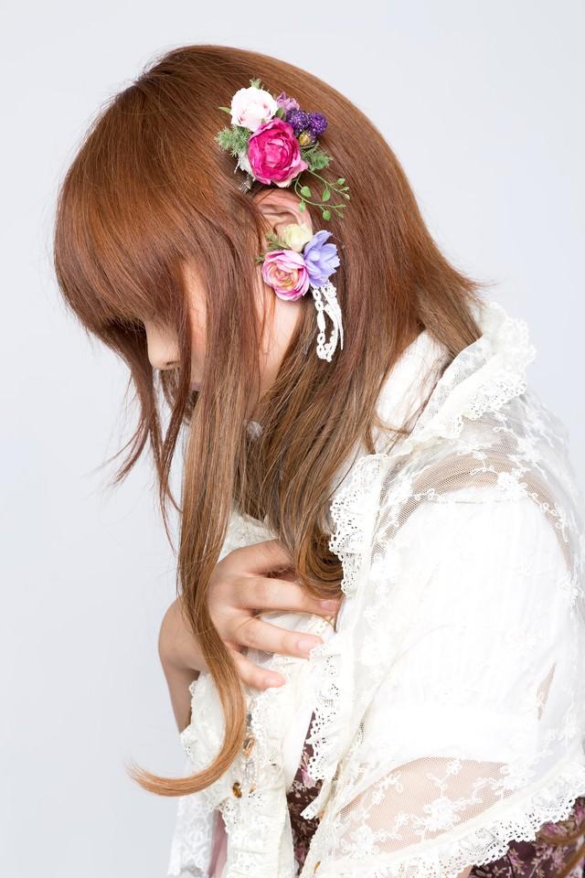 花のイヤリングをする女の子の写真