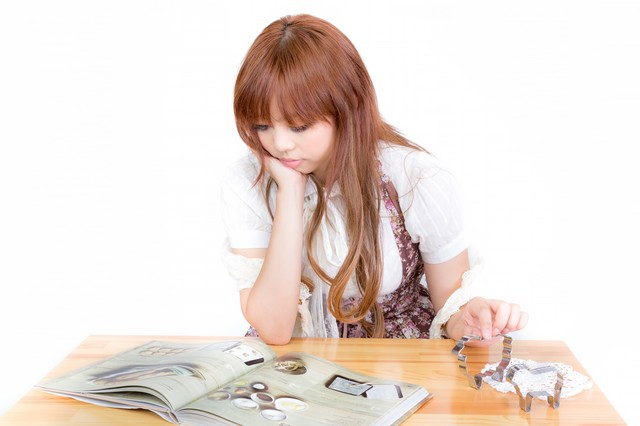 お菓子作りの本を読む女の子の写真