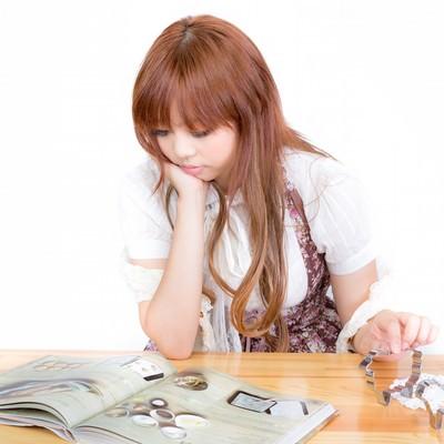 「お菓子作りの本を読む女の子」の写真素材