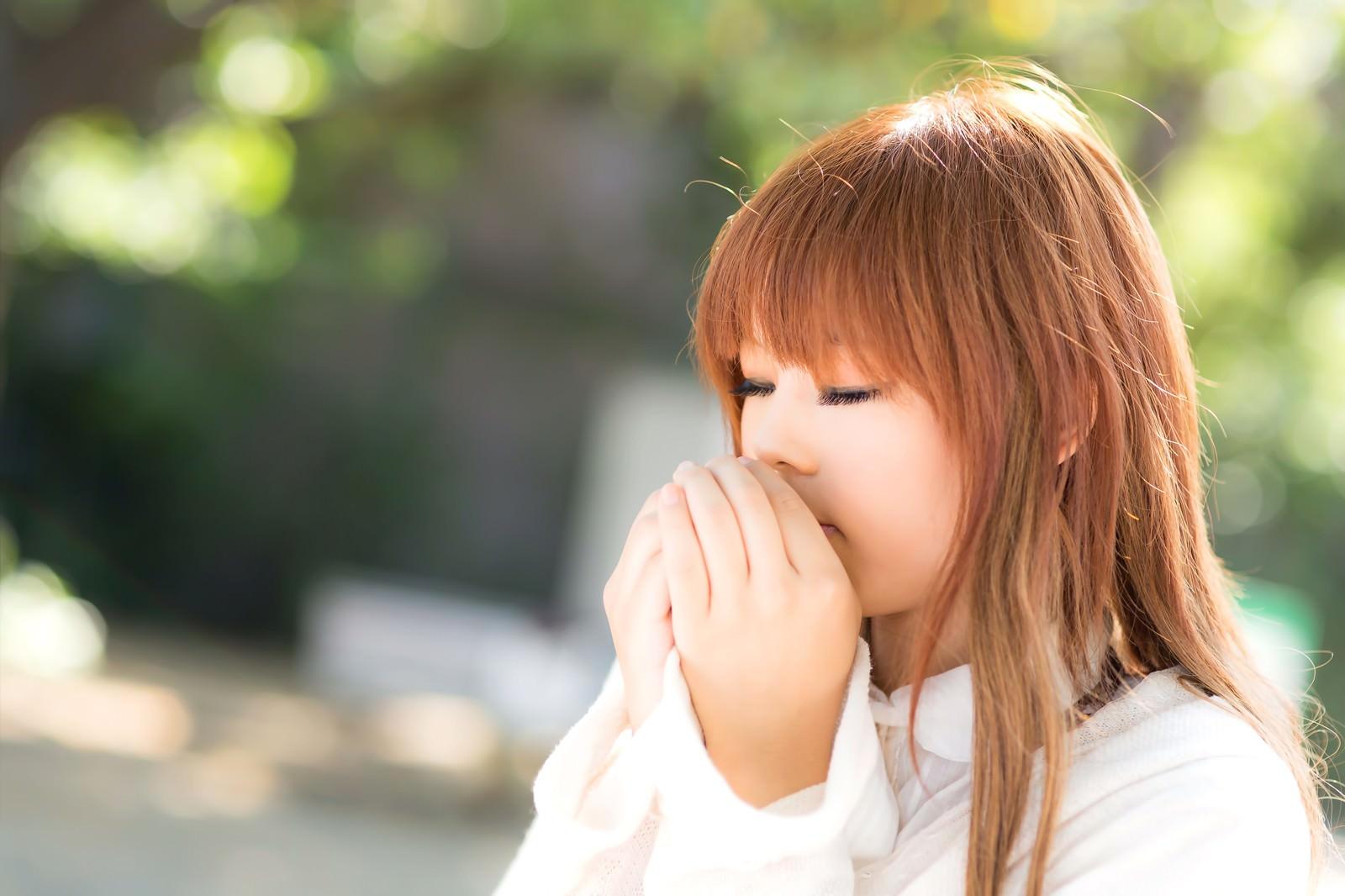 「口元で手を温める森ガール」の写真[モデル:あみ]