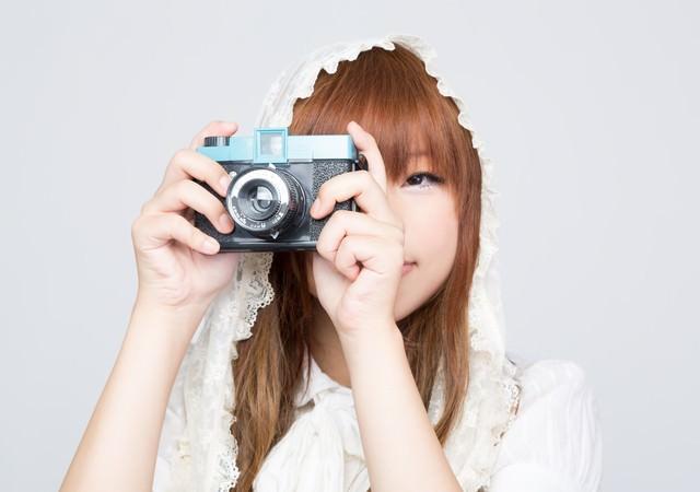 トイカメラのファインダーをのぞくゆるふわな女の子の写真