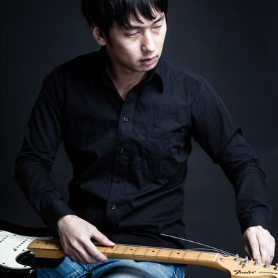 「ギターの弦を張り替えるギタリスト松野氏(仮)」の写真素材