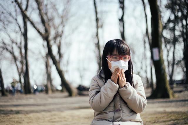花粉の飛散を気にする女の子の写真