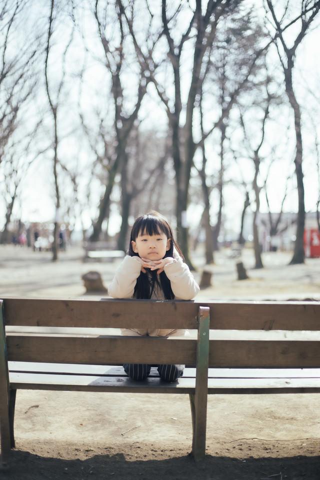 公園のベンチで退屈そうにする少女の写真