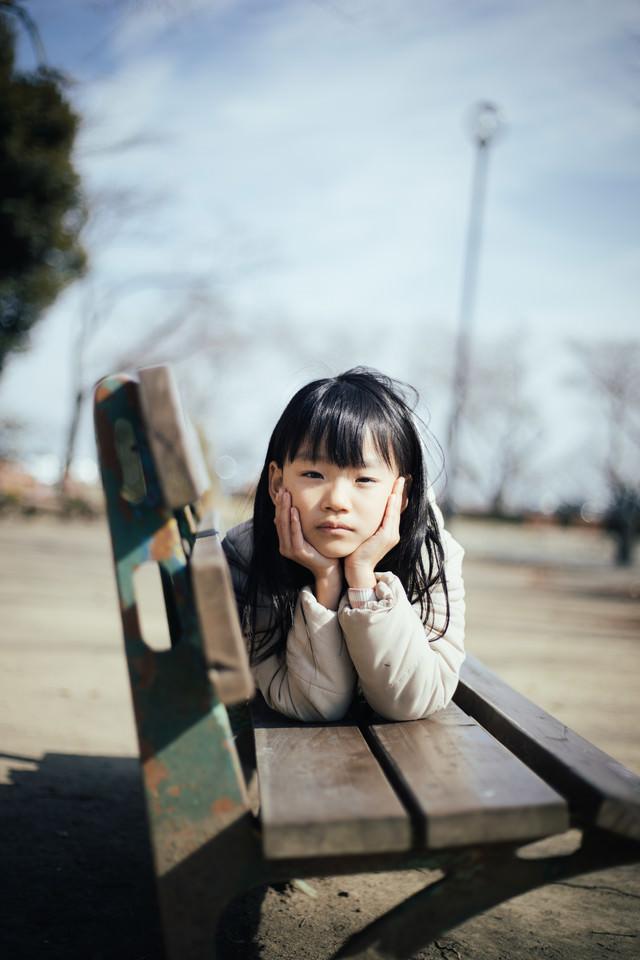 親同士の会話が盛り上がりすぎてベンチで暇そうにする女の子の写真