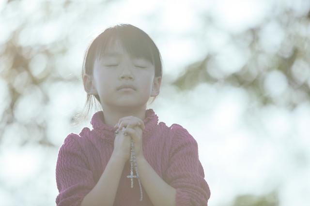 光の中で祈る少女の写真