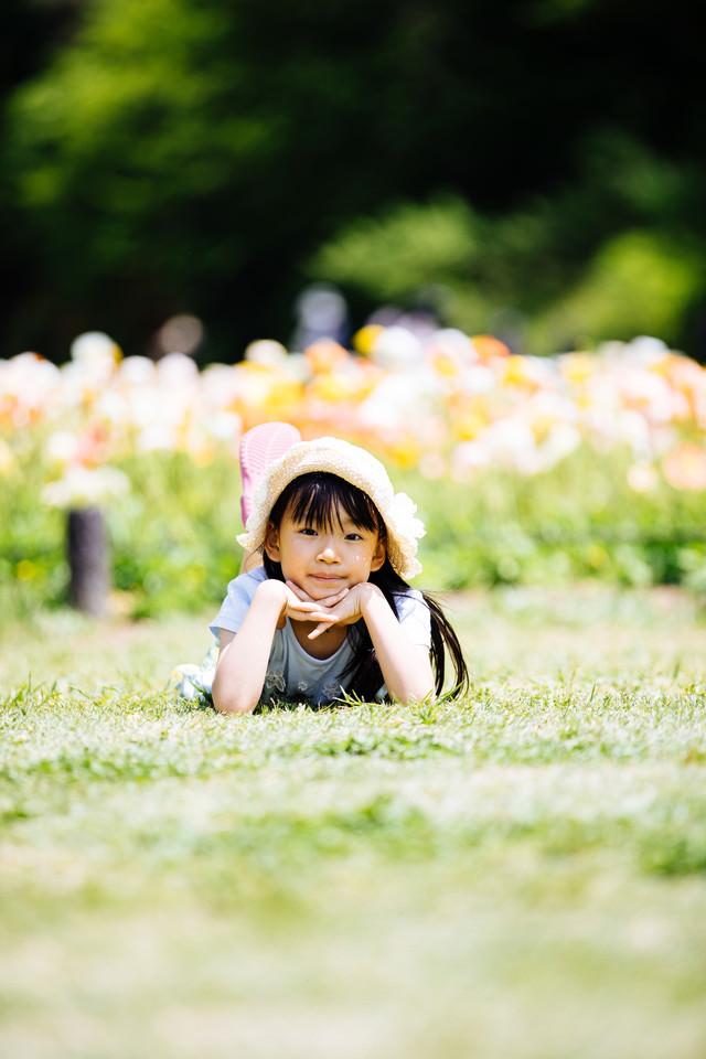 花畑の前で横になってくつろぐ麦わら帽子の女の子の写真