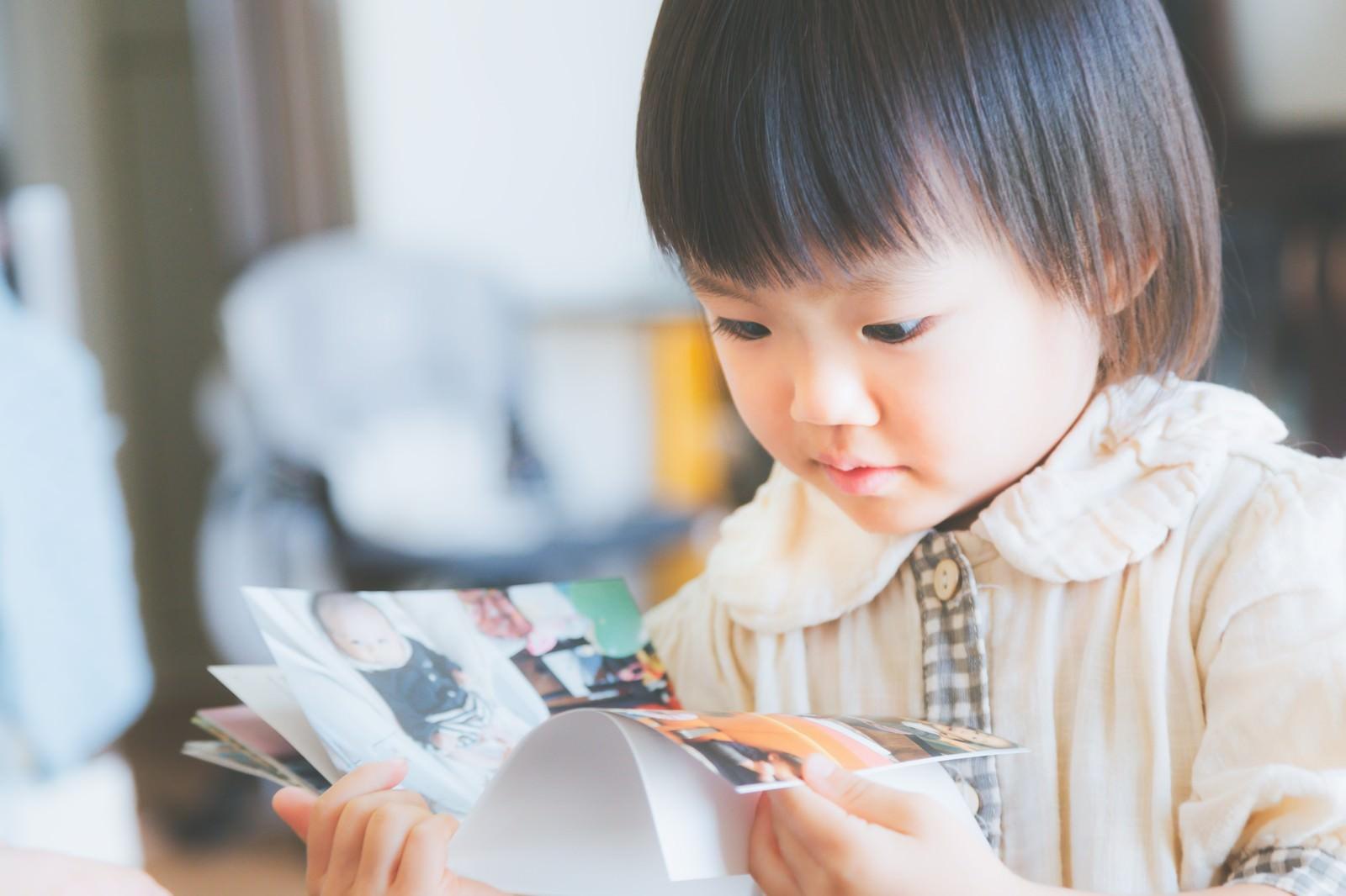 「アルバムを見る小さいな女の子」の写真[モデル:あんじゅ]