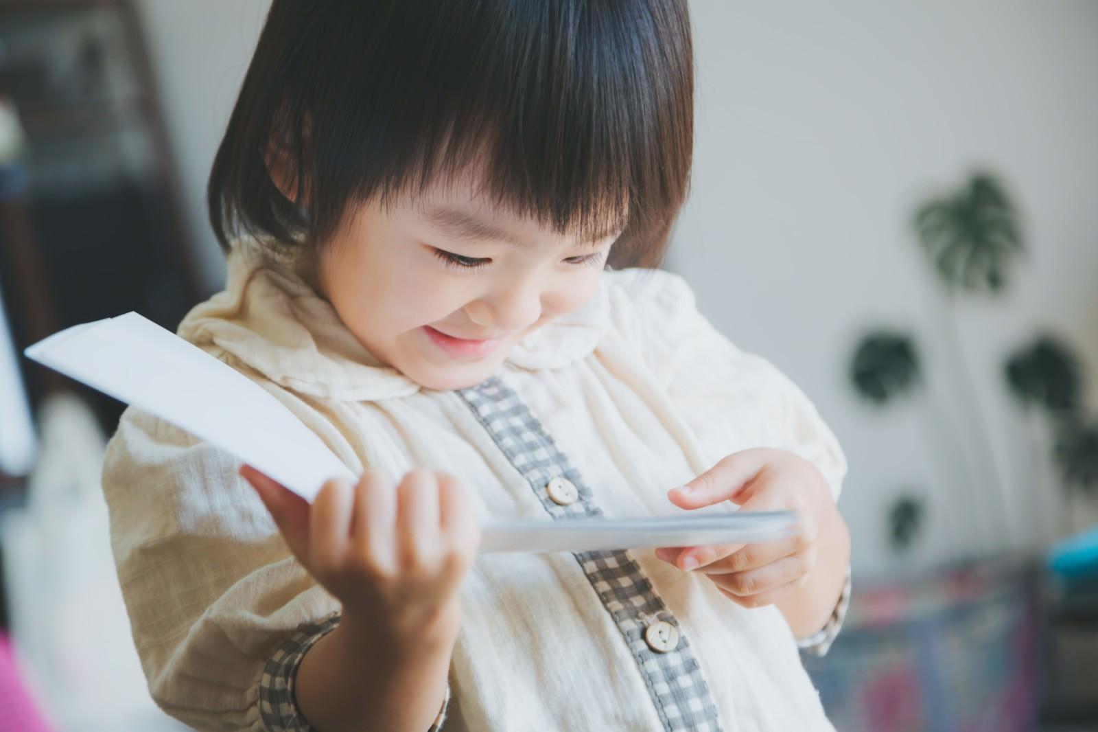 「お気に入りの絵本を読む女の子(子供)お気に入りの絵本を読む女の子(子供)」[モデル:あんじゅ]のフリー写真素材