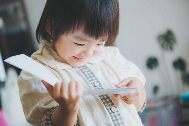 お気に入りの絵本を読む女の子(子供)の写真