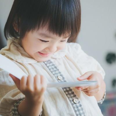 「お気に入りの絵本を読む女の子(子供)」の写真素材