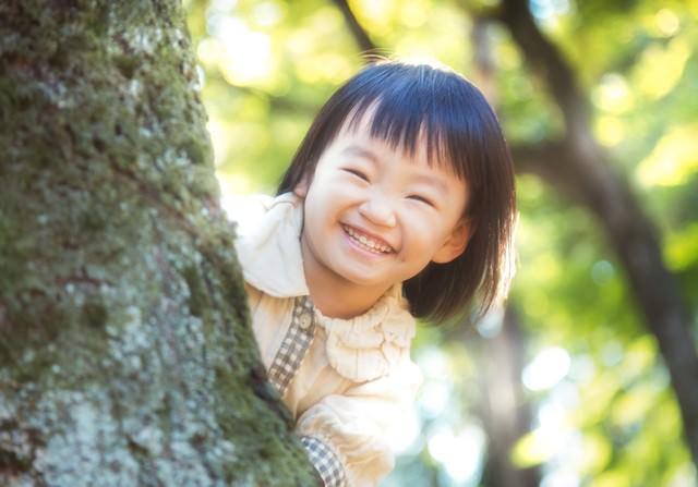 木陰からニコニコ笑顔の小さい女の子の写真