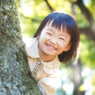 「木陰からニコニコ笑顔の小さい女の子」の写真素材