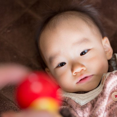 「おもちゃを欲しがる赤ちゃん」の写真素材