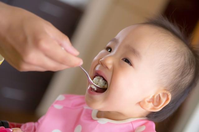 大きなお口でご飯をあーんする赤ちゃん