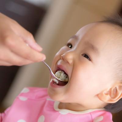 「大きなお口でご飯をあーんする赤ちゃん」の写真素材