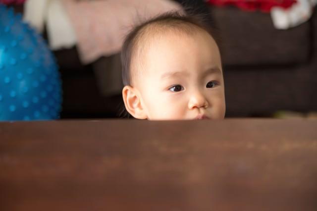 テーブルからひょこと顔を出したあかちゃんの写真
