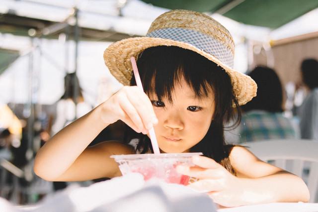 かき氷を食べる麦わら帽子の女の子の写真