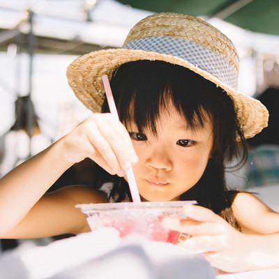 「かき氷を食べる麦わら帽子の女の子」の写真素材