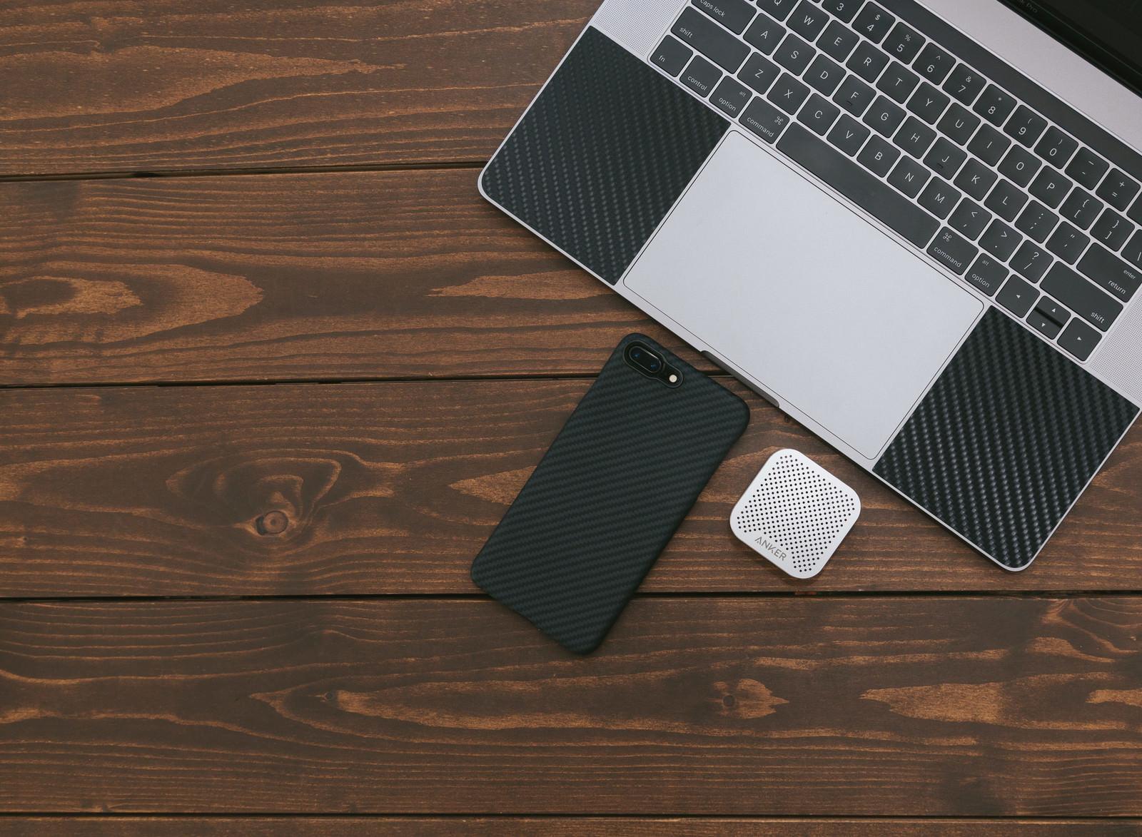 「スマートフォンと小型のワイヤレススピーカー」の写真