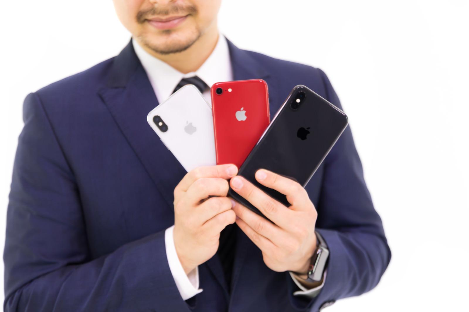 「歴代iPhone三機種を見せびらかすビジネスマン」の写真[モデル:Max_Ezaki]