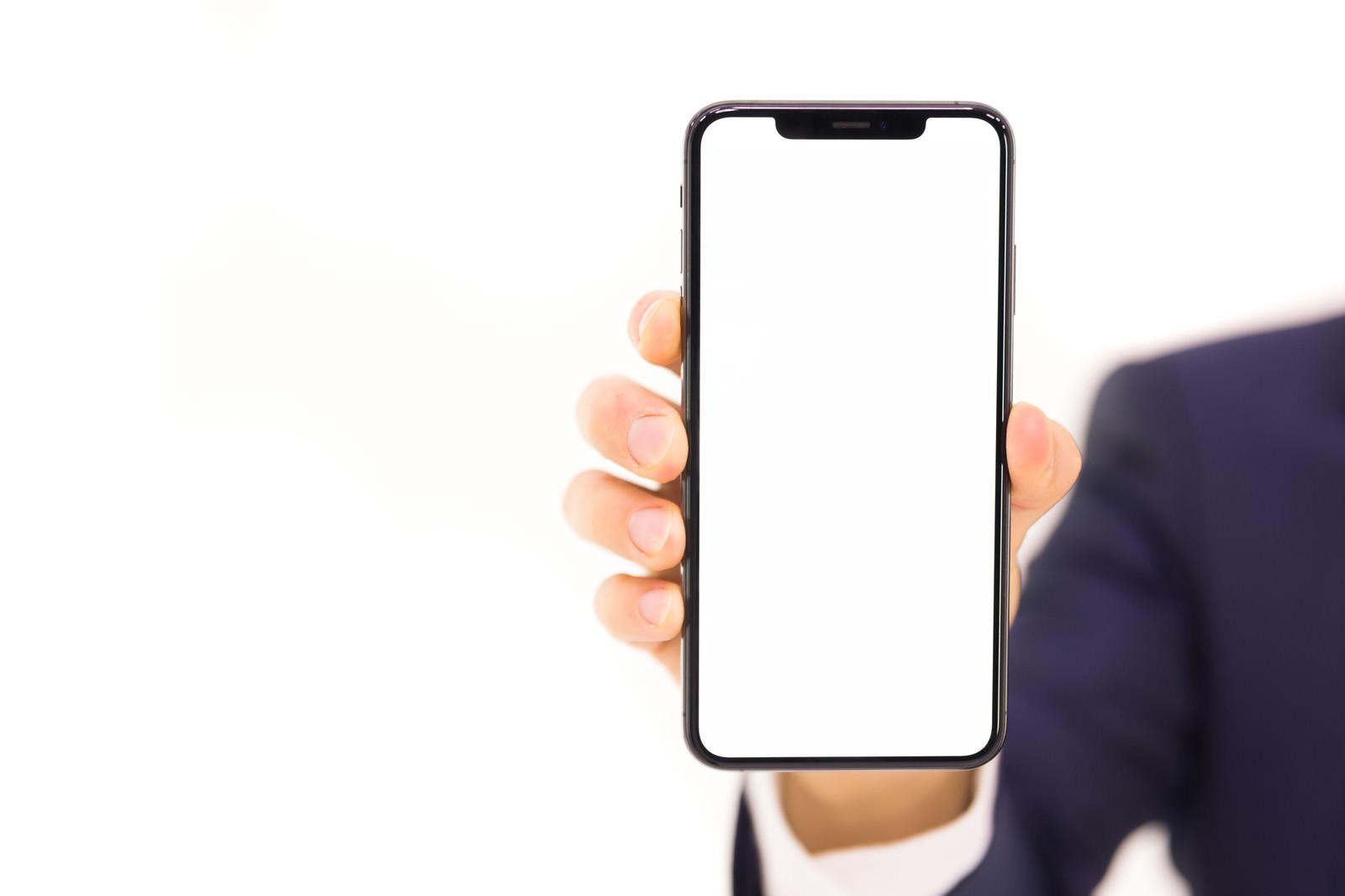 「iPhone XS Max の画面と本機を持つ手」の写真