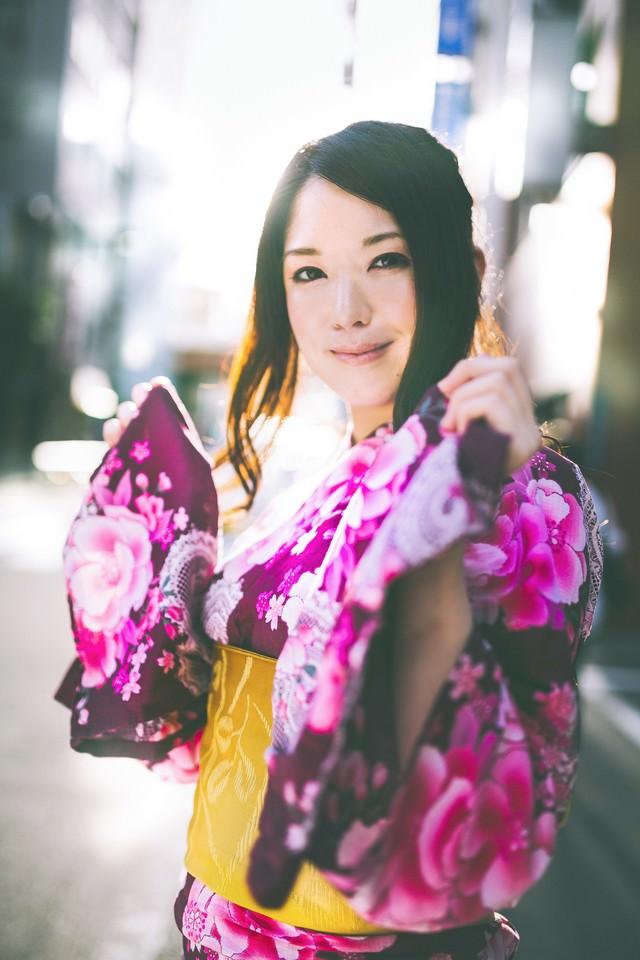 浴衣を見せて微笑む女性の写真