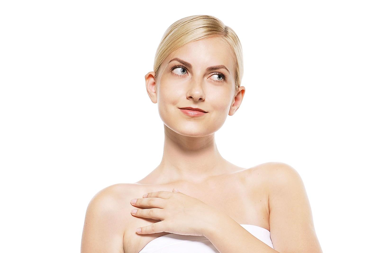 「胸に手を当てるホッとしたような表情の女性」の写真[モデル:モデルファクトリー]