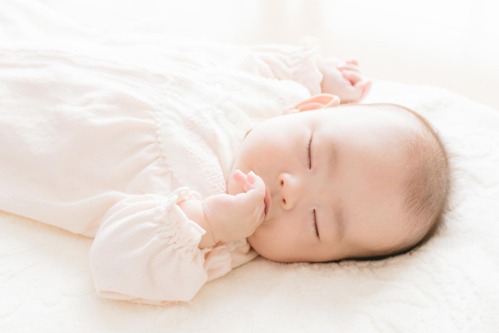 「指を咥える新生児」の写真