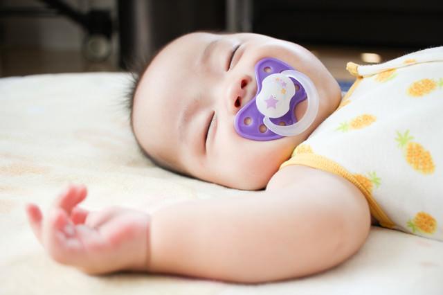 おしゃぶりを咥えてスヤスヤ赤ちゃんの写真