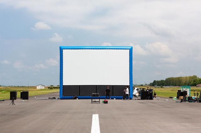 巨大スクリーンを準備するスタッフの写真