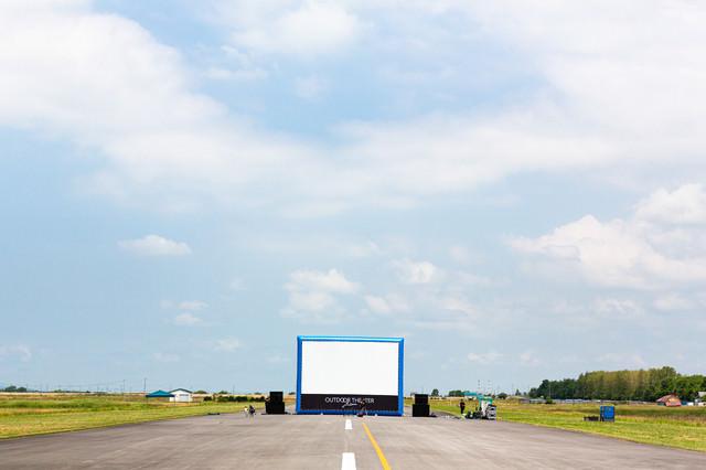 滑走路の上で野外シネマ用の巨大スクリーンを設営の写真