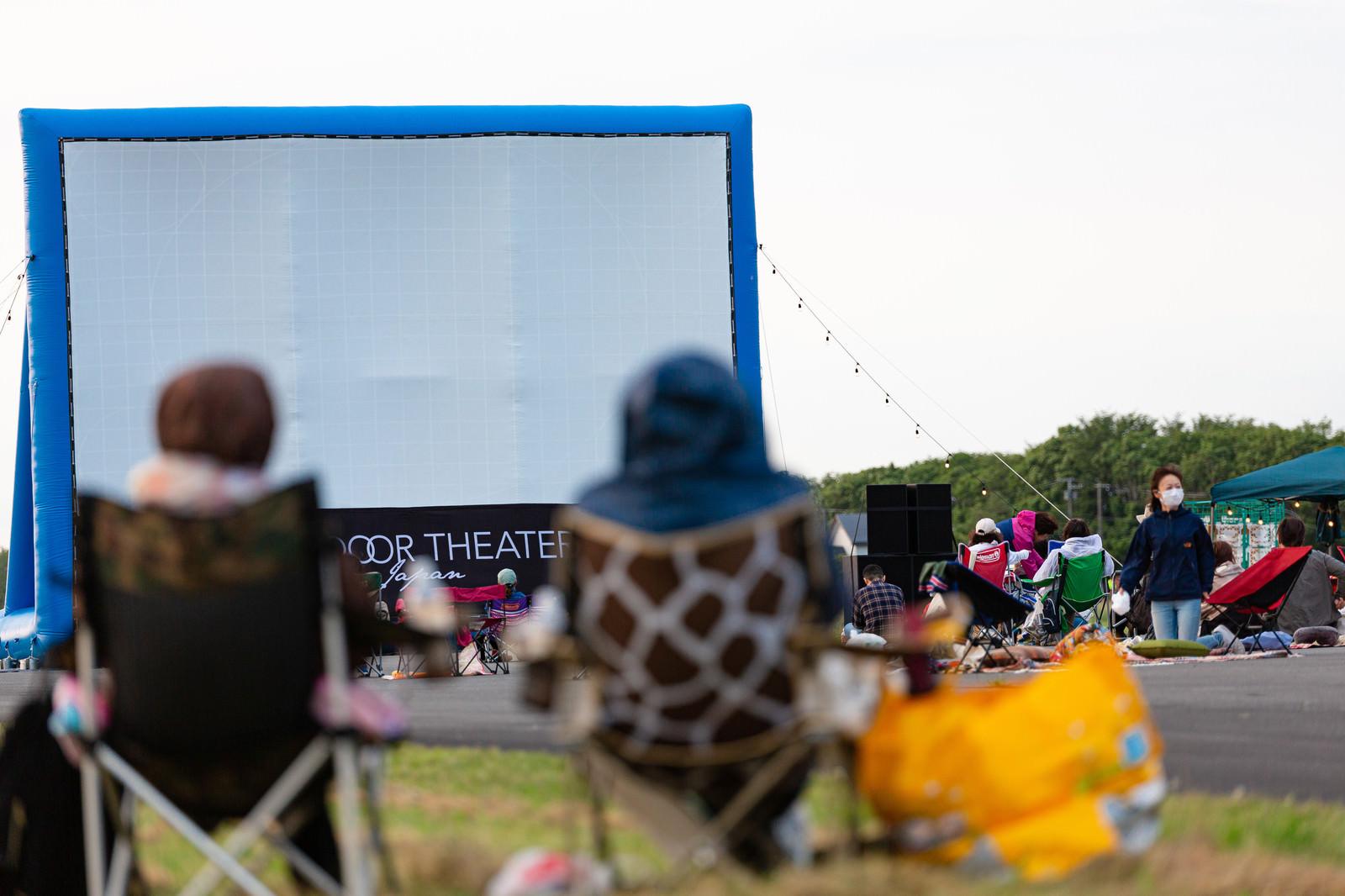 「観賞用の椅子などを持ち込み野外シネマを見る美唄の人たち」の写真