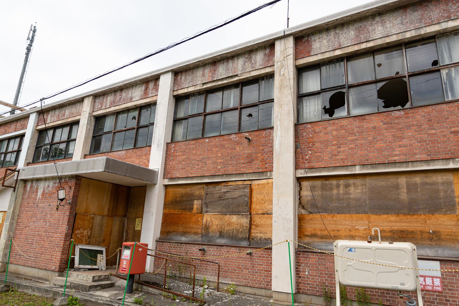 「窓ガラスが割られ廃墟感漂う美唄市我路郵便局」の写真