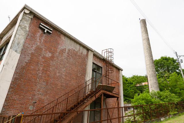 外壁が崩れる我路郵便局と煙突の写真