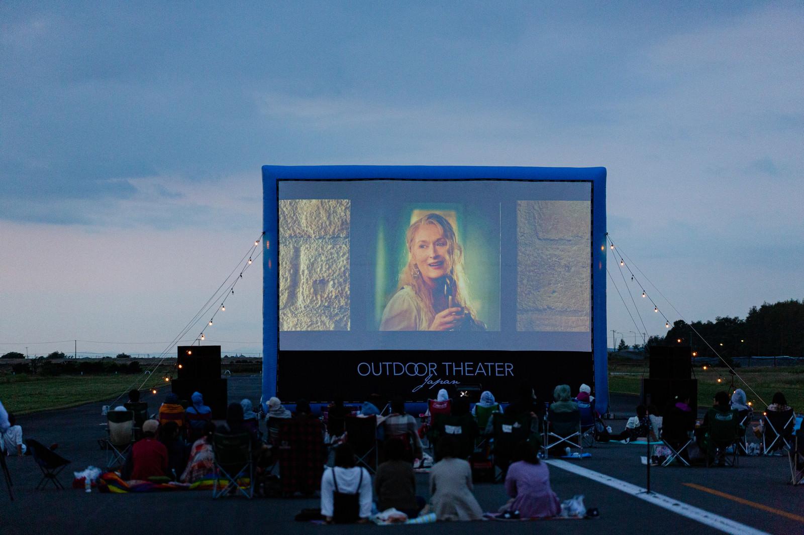 「滑走路で野外映画を楽しむ町の人々」の写真