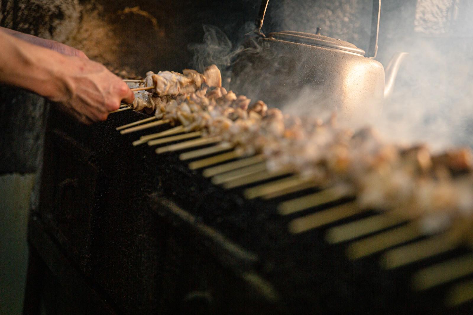 「一度に何本もの鳥串を焼く美唄焼き鳥の老舗店」の写真