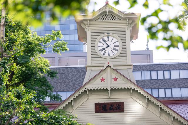 木陰から見る札幌市時計台(北海道札幌市中央区)の写真