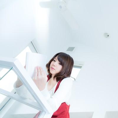 「吹き抜けの新築でマンガを読む女性」の写真素材
