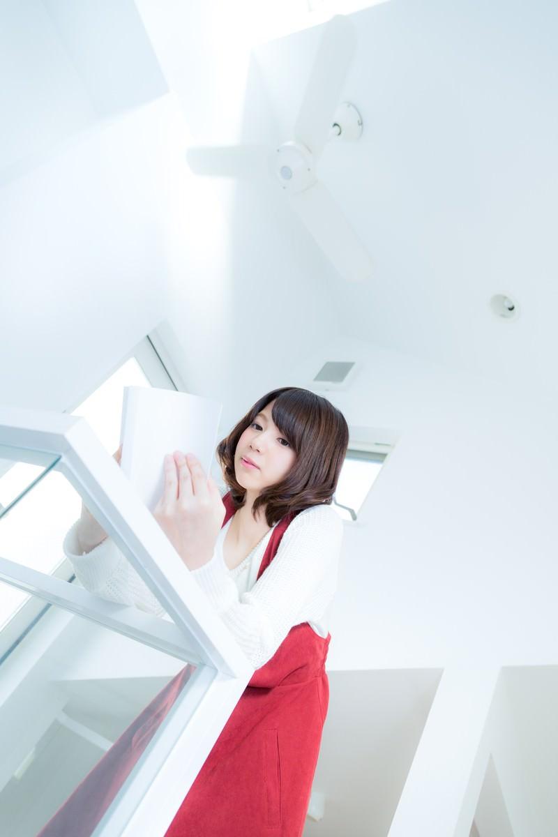 「吹き抜けの新築でマンガを読む女性」の写真[モデル:みき。]