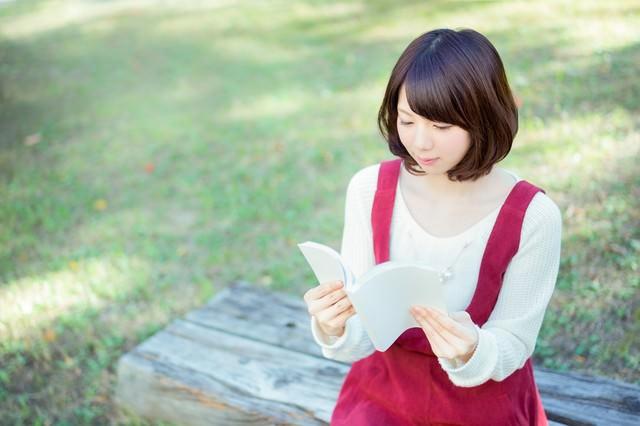 公園のベンチで読書する美女の写真