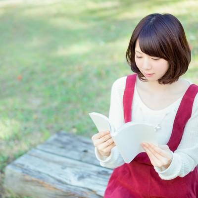 「公園のベンチで読書する美女」の写真素材