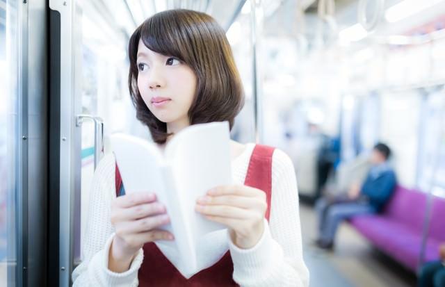 目的の駅までマンガを読む美少女の写真
