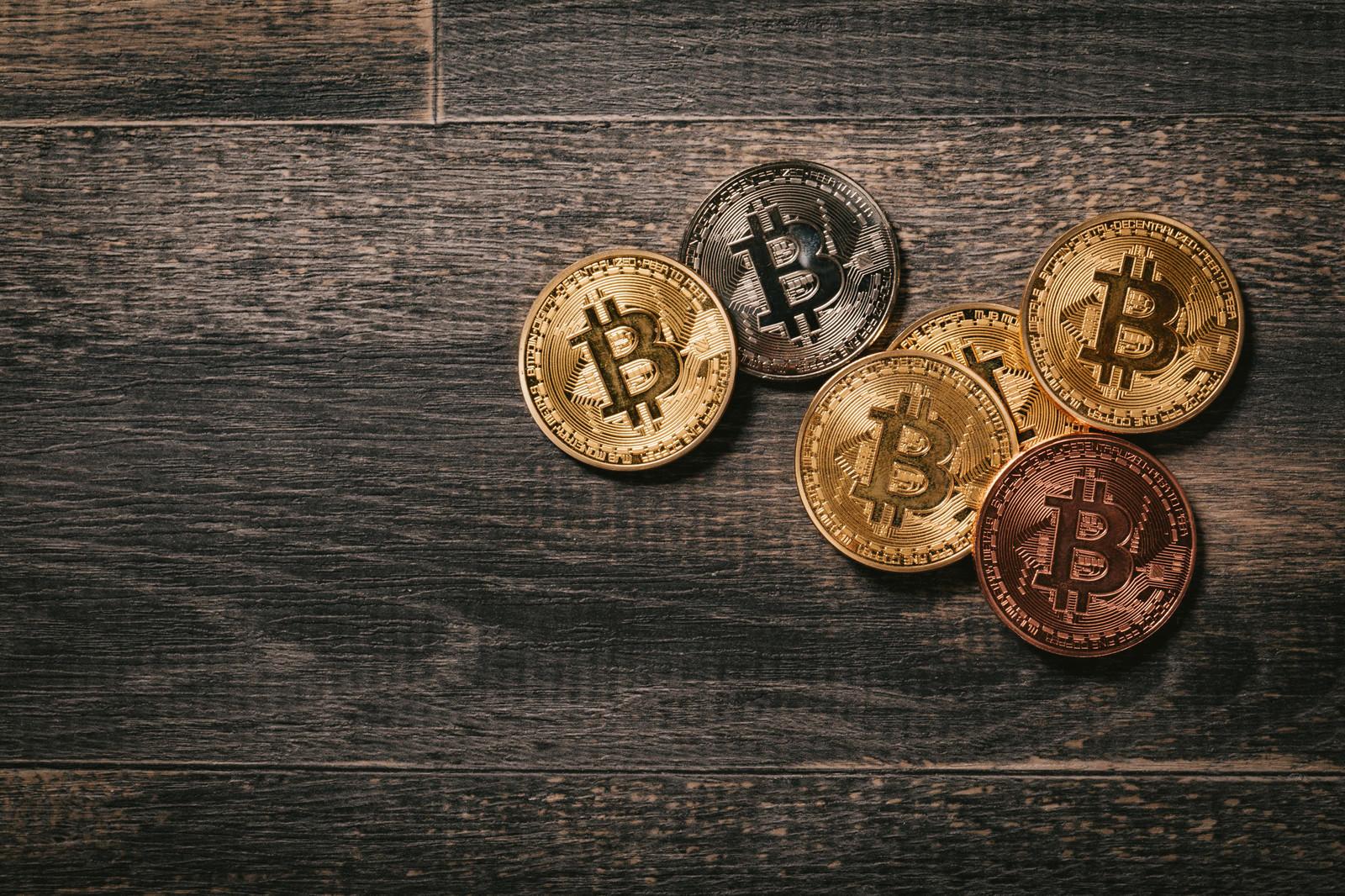「木目の板とビットコインのメダル」の写真