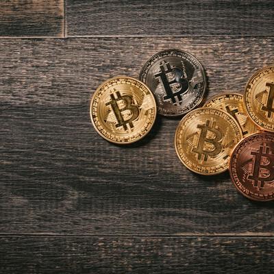 木目の板とビットコインのメダルの写真