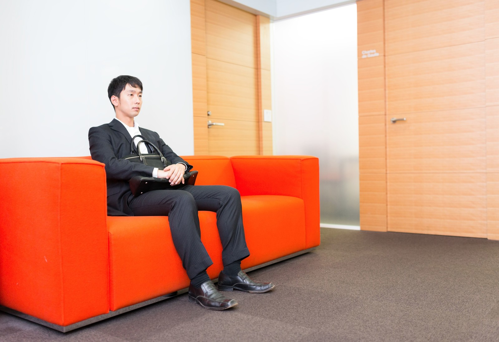 「大事な打ち合わせの前に待合室で緊張する新人営業マン」の写真[モデル:大川竜弥]