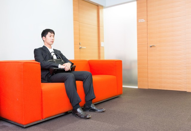 大事な打ち合わせの前に待合室で緊張する新人営業マンの写真