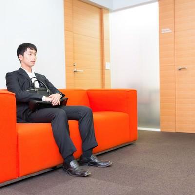 「大事な打ち合わせの前に待合室で緊張する新人営業マン」の写真素材